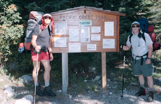 Peter and Pat holding up the signboard at White Chuck trailhead